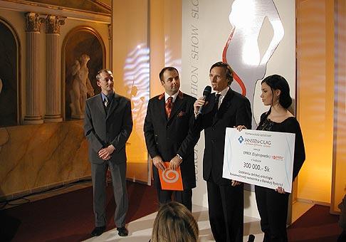Dr. Bician prevzal symbolický šek na sumu 300 000 Sk z rúk Dr. Lopašovského, generálneho riaditeľa spoločnosti Janssen-Cilag a Johnson and Johnson Company na European Fasion Show Slovakia 2004.
